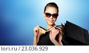 Купить «happy woman with credit card and shopping bags», фото № 23036929, снято 9 апреля 2016 г. (c) Syda Productions / Фотобанк Лори