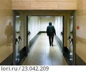 Человек в чёрной куртке с капюшоном, уходящий по длинному коридору морга. Стоковое фото, фотограф Игорь Травкин / Фотобанк Лори