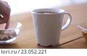 Купить «hand adding sugar to cup of tea and honey on table», видеоролик № 23052221, снято 15 апреля 2016 г. (c) Syda Productions / Фотобанк Лори