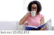 Купить «african woman reading book and drinking tea», видеоролик № 23052813, снято 7 мая 2016 г. (c) Syda Productions / Фотобанк Лори