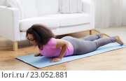 Купить «happy african woman exercising on mat at home», видеоролик № 23052881, снято 7 мая 2016 г. (c) Syda Productions / Фотобанк Лори
