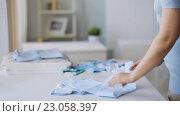 Купить «pregnant woman folding baby boys clothes at home 29», видеоролик № 23058397, снято 28 мая 2016 г. (c) Syda Productions / Фотобанк Лори