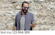 Купить «Man texting message on smartphone at stone wall», видеоролик № 23064389, снято 3 июня 2016 г. (c) Syda Productions / Фотобанк Лори
