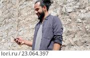 Купить «Man texting message on smartphone at stone wall», видеоролик № 23064397, снято 3 июня 2016 г. (c) Syda Productions / Фотобанк Лори