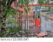 Купить «Двое рабочих в плащах собирают детскую площадку во дворе дома. Идет дождь», фото № 23065041, снято 7 июня 2016 г. (c) Наталья Николаева / Фотобанк Лори