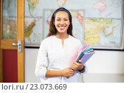 Купить «Portrait of smiling school teacher holding books in classroom», фото № 23073669, снято 6 марта 2016 г. (c) Wavebreak Media / Фотобанк Лори