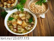 Купить «Гороховый суп с сухариками в тарелке на столе», фото № 23077173, снято 10 июня 2016 г. (c) Peredniankina / Фотобанк Лори