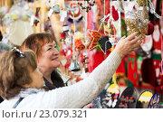 Купить «Happy mature women purchasing Christmas decorations», фото № 23079321, снято 20 марта 2019 г. (c) Яков Филимонов / Фотобанк Лори