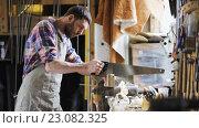 Купить «carpenter working with saw and wood at workshop», видеоролик № 23082325, снято 13 июня 2016 г. (c) Syda Productions / Фотобанк Лори