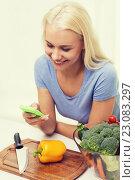 Купить «smiling woman with smartphone cooking vegetables», фото № 23083297, снято 26 апреля 2015 г. (c) Syda Productions / Фотобанк Лори