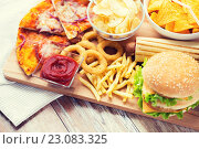 Купить «close up of fast food snacks on wooden table», фото № 23083325, снято 21 мая 2015 г. (c) Syda Productions / Фотобанк Лори