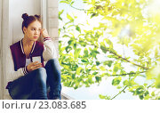 Купить «teenage girl sitting on windowsill with smartphone», фото № 23083685, снято 19 декабря 2015 г. (c) Syda Productions / Фотобанк Лори