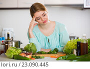Купить «Young housewife tired of cooking vegetables in domestic kitchen», фото № 23090445, снято 24 июня 2019 г. (c) Яков Филимонов / Фотобанк Лори