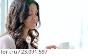 Купить «Young girl drinking a coffee», видеоролик № 23091597, снято 10 июня 2016 г. (c) Raev Denis / Фотобанк Лори