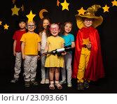Купить «Веселые дети стоят на черном фоне со звездами. Девочка держит в руках телескоп», фото № 23093661, снято 2 апреля 2016 г. (c) Сергей Новиков / Фотобанк Лори