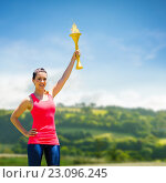 Composite image of sporty woman posing and smiling with olympic torch. Стоковое фото, агентство Wavebreak Media / Фотобанк Лори