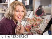 Купить «Женщина выбирает губную помаду в магазине», фото № 23099905, снято 29 февраля 2016 г. (c) Татьяна Яцевич / Фотобанк Лори