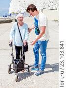 Купить «An Elderly Disabled Woman Using A Rollator Walking Aid Helped By Her Grandson, Brighton, Sussex, UK.», фото № 23103841, снято 17 мая 2016 г. (c) age Fotostock / Фотобанк Лори