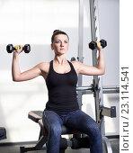 Красивая спортивная женщина делает силовые фитнес упражнения в тренажерном зале. Стоковое фото, фотограф Nikolay Safronov / Фотобанк Лори