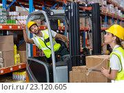Купить «Focus of worker sitting on a pallet truck is pointing shelves», фото № 23120605, снято 23 марта 2016 г. (c) Wavebreak Media / Фотобанк Лори