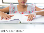 Купить «Midsection of blind girl reading braille book», фото № 23138897, снято 9 апреля 2016 г. (c) Wavebreak Media / Фотобанк Лори