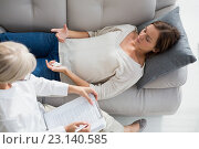 Купить «High angle view of woman lying on sofa by therapist», фото № 23140585, снято 5 апреля 2016 г. (c) Wavebreak Media / Фотобанк Лори