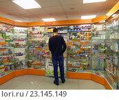 Купить «Молодой мужчина покупает медицинские препараты в аптеке», эксклюзивное фото № 23145149, снято 10 июня 2016 г. (c) Елена Осетрова / Фотобанк Лори