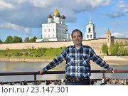 Молодой мужчина стоит на смотровой площадке на фоне Троицкого собора. Стоковое фото, фотограф Максим Мицун / Фотобанк Лори