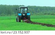 Купить «Молодой тракторист пашет на тракторе в дождь», видеоролик № 23152937, снято 24 июня 2016 г. (c) Сергей Буторин / Фотобанк Лори