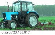Купить «Молодой тракторист пашет на тракторе в дождь», видеоролик № 23155817, снято 24 июня 2016 г. (c) Сергей Буторин / Фотобанк Лори