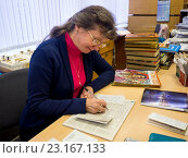 Купить «Библиотекарь сидя за столом заполняет формуляры читателей», эксклюзивное фото № 23167133, снято 22 марта 2016 г. (c) Вячеслав Палес / Фотобанк Лори