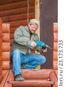 Купить «Worker with a drill in safety glasses working in a wooden cottage.», фото № 23173733, снято 17 мая 2015 г. (c) easy Fotostock / Фотобанк Лори