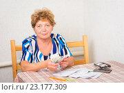 Купить «Пожилая женщина с квитанциями и деньгами за столом», фото № 23177309, снято 5 июня 2016 г. (c) Типляшина Евгения / Фотобанк Лори