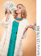 Купить «Young woman in a fur coat holding money», фото № 23178965, снято 30 января 2016 г. (c) Art Konovalov / Фотобанк Лори