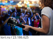 Купить «female singer playing guitar over happy fans crowd», фото № 23186625, снято 20 октября 2014 г. (c) Syda Productions / Фотобанк Лори