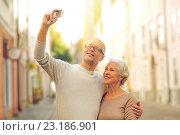 Купить «senior couple photographing on city street», фото № 23186901, снято 4 сентября 2014 г. (c) Syda Productions / Фотобанк Лори