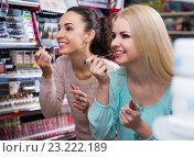 Купить «Happy young women choosing lip lacquer», фото № 23222189, снято 23 октября 2018 г. (c) Яков Филимонов / Фотобанк Лори