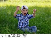 Купить «Мальчик в бейсболке сидит на траве и изображает хищника», фото № 23224781, снято 2 июля 2020 г. (c) Олег Белов / Фотобанк Лори