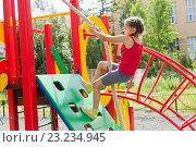 Девочка ловко забирается на стенку по канату на детской спортивной площадке. Стоковое фото, фотограф Лариса Капусткина / Фотобанк Лори