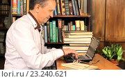 Купить «Мужчина работает за ноутбуком в библиотеке», видеоролик № 23240621, снято 11 мая 2016 г. (c) Валерий Бочкарев / Фотобанк Лори