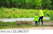 Купить «Сестра с младшим братом играют возле реки», видеоролик № 23246517, снято 21 октября 2015 г. (c) Владимир Кравченко / Фотобанк Лори