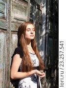 Купить «Молодая девушка на фоне старого деревянного здания», фото № 23257541, снято 12 июля 2016 г. (c) Момотюк Сергей / Фотобанк Лори