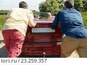Купить «happy friends pushing broken cabriolet car», фото № 23259357, снято 28 мая 2016 г. (c) Syda Productions / Фотобанк Лори