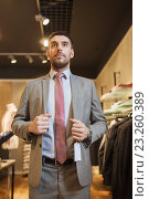 Купить «young man trying suit at clothing store», фото № 23260389, снято 1 апреля 2016 г. (c) Syda Productions / Фотобанк Лори