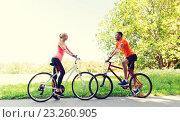 Купить «happy couple riding bicycle outdoors», фото № 23260905, снято 5 июля 2015 г. (c) Syda Productions / Фотобанк Лори