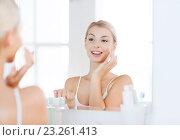 Купить «happy woman applying cream to face at bathroom», фото № 23261413, снято 13 февраля 2016 г. (c) Syda Productions / Фотобанк Лори