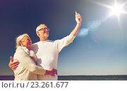 Купить «seniors with smartphone taking selfie on beach», фото № 23261677, снято 18 августа 2015 г. (c) Syda Productions / Фотобанк Лори