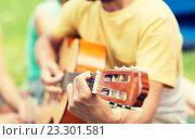 Купить «close up of man playing guitar at camping», фото № 23301581, снято 25 июля 2015 г. (c) Syda Productions / Фотобанк Лори