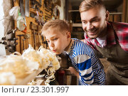 Купить «father and little son with wood plank at workshop», фото № 23301997, снято 14 мая 2016 г. (c) Syda Productions / Фотобанк Лори