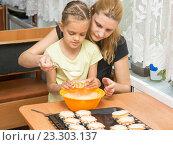 Купить «Мама и семилетняя дочка наливают тесто в форму для запекания кексов», фото № 23303137, снято 3 апреля 2016 г. (c) Иванов Алексей / Фотобанк Лори